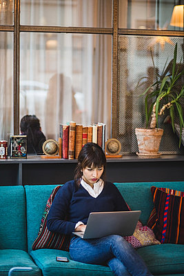 Confident businesswoman using laptop on sofa at creative office - p426m2088921 by Maskot