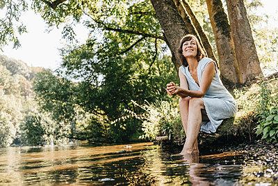 Mature woman relaxing on the riverbank - p586m1171858 by Kniel Synnatzschke