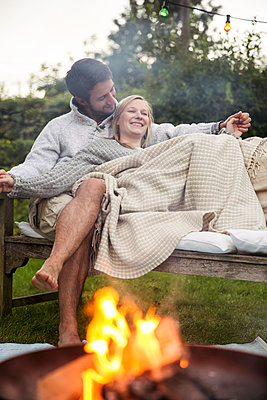 Young couple cuddling on garden bench - p788m1165291 by Lisa Krechting