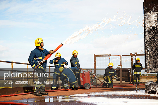 Firemen training, firemen spraying firefighting foam at training facility - p429m2058301 by Peter Muller