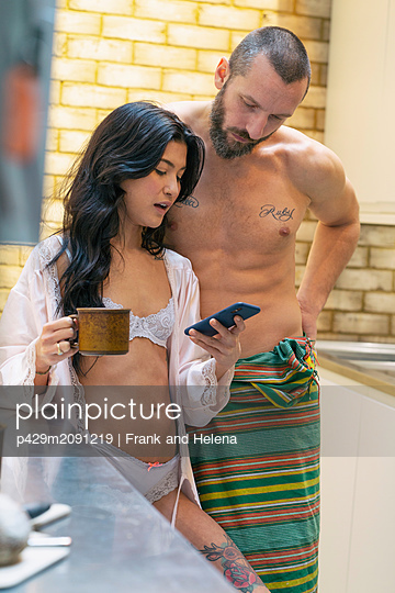 Hipster couple using smartphone in kitchen - p429m2091219 by Frank and Helena