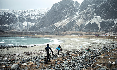 Two surfers wearing wetsuits and carrying surfboards walking along a beach with mountains behind. - p1100m1482228 by Mint Images