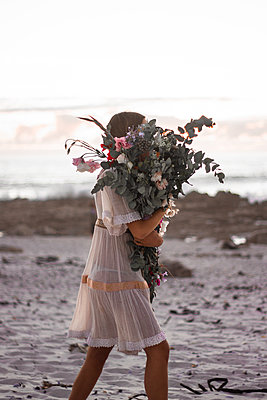 Teenage girl carries bunch of flowers across the beach - p1640m2246201 by Holly & John
