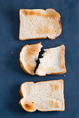 Toasted bread slices on blue background, broken-up - p300m1047560f by Mandy Reschke
