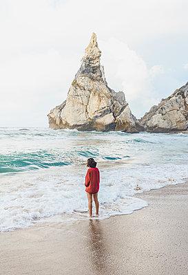 Young woman standing on shore at Praia da Ursa, Lisboa, Portugal - p300m2198209 by KIVISER