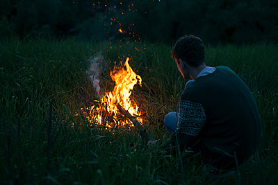 Caucasian man with campfire at night - p555m1504179 by Dmitriy Bilous
