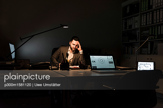 Businessman working in office at night - p300m1581120 by Uwe Umstätter