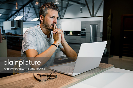 Thoughtful mature businessman working while looking at laptop in office - p300m2221640 by Rafa Cortés