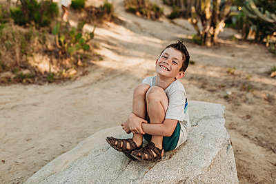 Portrait of older boy sitting on rock and smiling in cactus garden - p1166m2136682 by Cavan Images