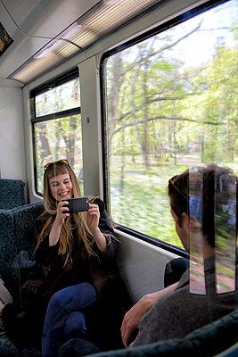 Junge Frau fotografiert jungen Mann in der Bahn - Reflexion - p1212m1138823 von harry + lidy