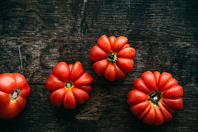 Four homegrown organic oxheart tomatoes on dark wood - p300m1166514 by Ina Peters