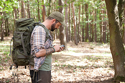 Man with backpack on a hiking trip in forest using cell phone - p300m1499629 by Michelle Fraikin