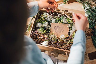 Woman arranging flowers in a box, partial view - p300m1581246 von Gustafsson