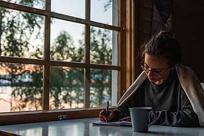 Finland, Lapland, young woman sitting at the window at a lake writing into diary - p300m2060828 by Kike Arnaiz