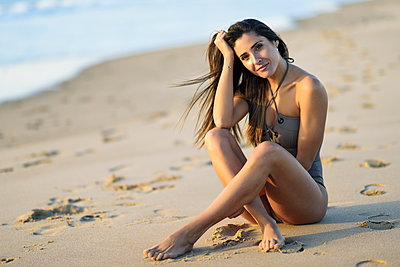 Portrait of beautiful woman wearing swimsuit sitting on the beach - p300m2080837 by Javier Sánchez Mingorance