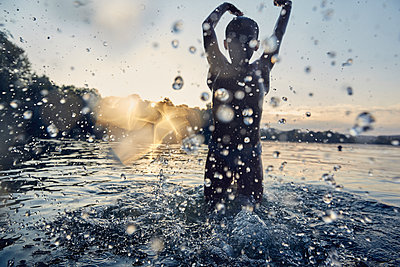 Silhouette of a girl splashing in a lake by sunset - p300m2180058 by Stefanie Aumiller