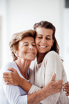 Smiling woman and granddaughter embracing each other at home - p300m2276922 by Gustafsson