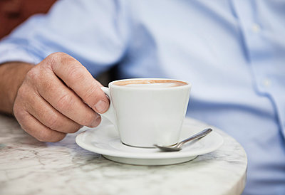 Close up of mature man holding a cup of coffee at cafe - p426m1093438f by Maskot