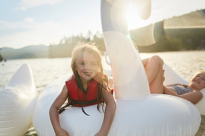 Girls playing on inflatable swan in lake - p924m2090695 by heshphoto
