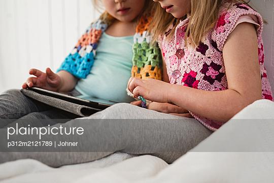 Girls using digital tablet - p312m2121789 by Johner