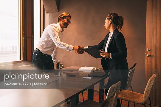 plainpicture - plainpicture p426m2127779 - Female lawyer shaking hands... - DEEPOL by plainpicture