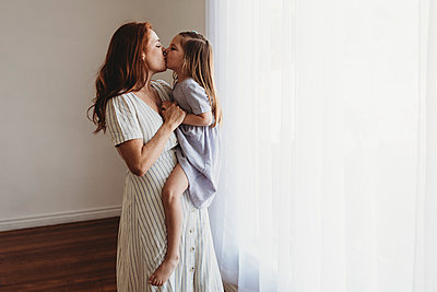 Side view of young mother holding daughter and kissing in studio - p1166m2130917 by Cavan Images