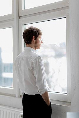 Junger Mann schaut aus dem Fenster - p1212m1119430 von harry + lidy