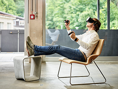 Man wearing VR glasses sitting on chair - p300m1550248 by Christian Vorhofer