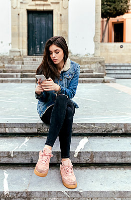 Young woman sitting on stairs in a town checking her smartphone - p300m1568276 by Marco Govel