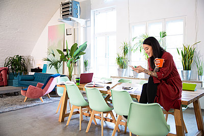 Smiling woman using cell phone in modern office - p300m2114279 by Florian Küttler