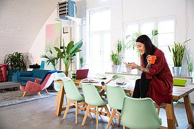 Smiling woman using cell phone in modern office - p300m2114279 von Florian Küttler