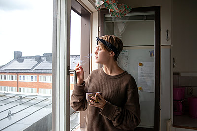Woman smoking cigarette at window - p312m2191223 by Marie Linnér