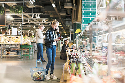 Girl using smart phone while reading label on bottle in organic groceries store - p426m1407370 by Kentaroo Tryman