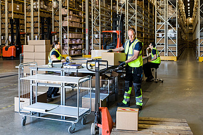 Multi-ethnic coworkers working at distribution warehouse - p426m2018792 by Maskot