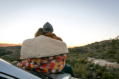 Rear view of young couple by mountains on car bonnet wrapped in patchwork blanket, Chilao Campgrounds, Los Angeles, California, USA - p429m1118336 by Alyson Aliano