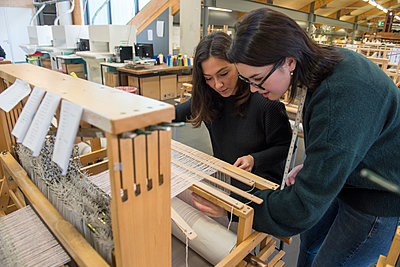 Students weaving with loom in textile workshop - p429m2252441 by G. Mazzarini