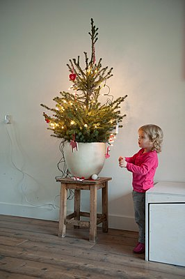 Child decorating a christmas tree - p896m959438 by Sabine Joosten