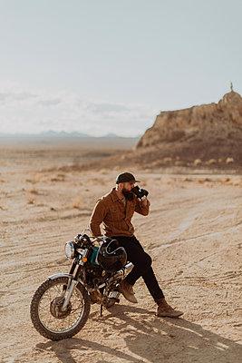Motorcyclist enjoying drink on stationary bike, Trona Pinnacles, California, US - p924m2068175 by Peter Amend