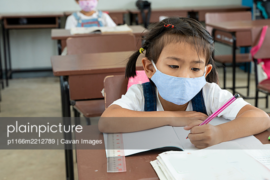 Elementary student with face mask back at school after covid-19 - p1166m2212789 by Cavan Images