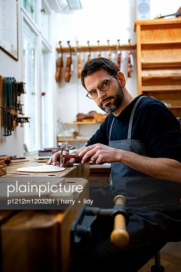 Geigenbauer an der Werkbank und arbeitet an der Geigendecke - p1212m1203281 von harry + lidy