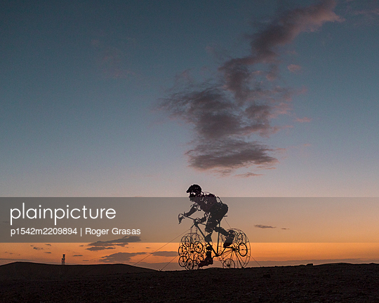 Sculpture of a cyclist against setting sun - p1542m2209894 by Roger Grasas