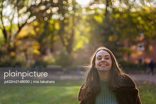 Glückliche junge Frau im Park - p432m2148090 von mia takahara
