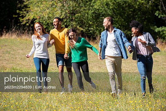 Happy young friends walking together in public park - p623m2294839 by Eric Audras