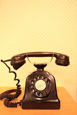 Schwarzes Retro Telefon vor Tapete - p045m1059301 von Jasmin Sander