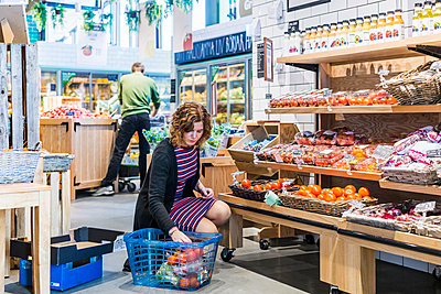 Young woman buying tomatoes while crouching in supermarket - p1264m1173198 by Astrakan