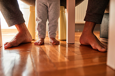 Father's and little daughter's feet barefoot on parquet - p300m2059576 by Zeljko Dangubic