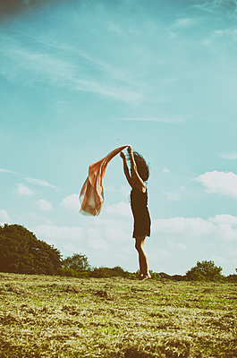 Young woman throwing a a piece of fabric in the field  - p794m1146130 by Mohamad Itani