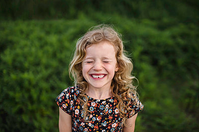 Portrait of girl with wavy blond hair and missing tooth in field - p924m1468783 by Erin Lester