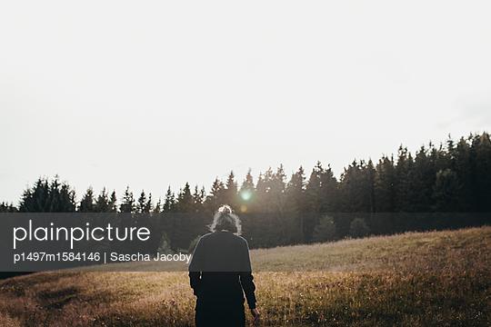 Junge Frau läuft über grüne Wiese in der Natur im Sonnenuntergang - p1497m1584146 von Sascha Jacoby