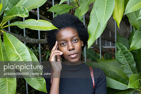 African woman between green leaves, portrait - p1640m2260035 by Holly & John